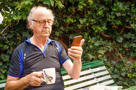 Meneer kijkt op zijn telefoon terwijl hij koffie drinkt op een bankje