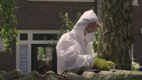 Persoon in beschermende kleding haalt golfplaat van asbestdak