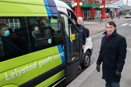 De heer Schut van Arriva zit in de bus met het zwarte mondkapje, wethouder Baaten staat naast de bus en de heer Cassé staat in de deuropening van de bus.