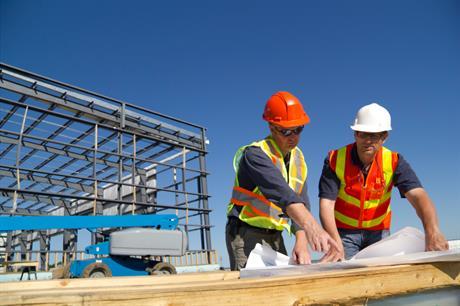 Bouwvakkers bekijken bouwtekening bedrijfspand