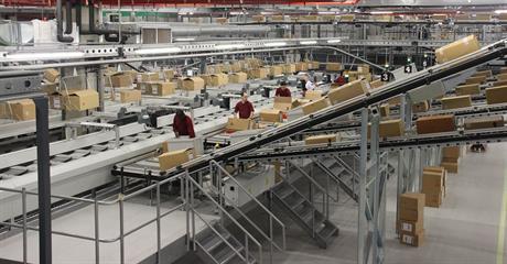Medewerkers plaatsen dozen op lopende banden in productiehal