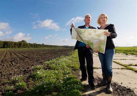 Man en vrouw met kaart in weiland
