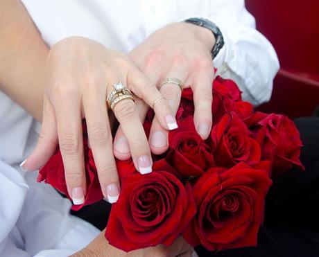 Bruidspaar met trouwringen en bos rozen