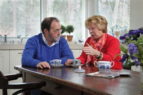 Ouder echtpaar in gesprek aan tafel in huis